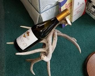 This is an empty wine bottle to show that this is an antler wine rack.
