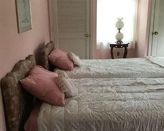 Pair of twin beds with upholstered headboards.