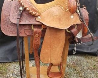 Hand tooled two rig Simco saddle with white lacing and metal work. https://ctbids.com/#!/description/share/314366