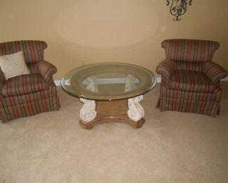 The glass on this round table is beveled sitting atop 4 pillars on a wood base