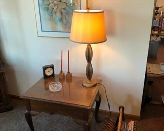 Small square table with lamp and artwork and magazine rack