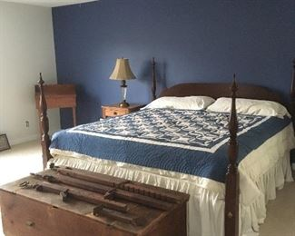 King size bed, quilt, large antique trunk.