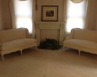 Master Bedroom:  Two matching down filled settees by SAM MOORE are upholstered in a beautiful ivory fabric.  They flank a faux fireplace surround, print and ferns.  Closer photos are coming up!
