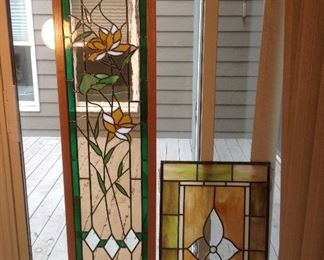 """Master Bedroom:  Two stained glass window decorations are shown.  The hanging one on the left has a wooden frame and measures 16-l/2"""" wide x 60"""" tall; the one on the right has a lead trim frame and hanging chains and measures 19-l/4"""" wide x 31"""" tall."""