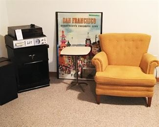 Mid-century armchair. Brass footed table with Formica top.  Mengel nightstand/end table. 8 track player. Poster by Doug Kingman.