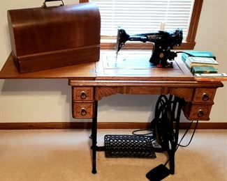 Singer treadle has electric Singer sewing machine & attachments