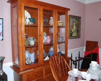 Cabinet with many collectible pottery pieces