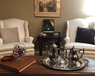Match set of two ivory wing back chairs, drop leaf coffee table, coffee and tea silver plated set, Oval mahogany side table with drawer and black marble top, framed print, and more