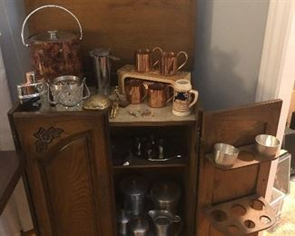 Freestanding bar with an extensive collection of barbare including: copper mugs, ice bucket, glass martini ice bucket,  stainless steel service ware and more
