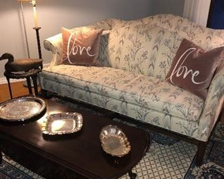Matched set of two single cushion loveseats, floor lamp, iron side table with glass top, hand carved decoy, mahogany coffee table with drop leaf, and large area rug