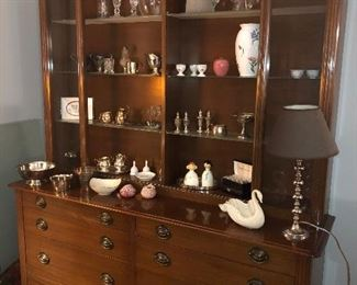 Eight drawer serving hutch with sliding glass doors (lit).  Inside:  Tiffany vase,  Sterling silver pieces, Lenox, marble, silver-plated, and pottery collectibles