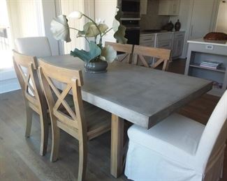 Cement table top and with four solid wood chairs and two fabric covered accent end chairs