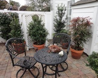 Vintage Style Outdoor cast iron patio furniture. Potted plants and accessories.