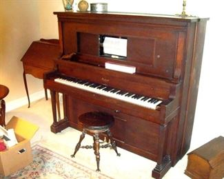 Beckwith player piano with several piano rolls, Antique piano stool.