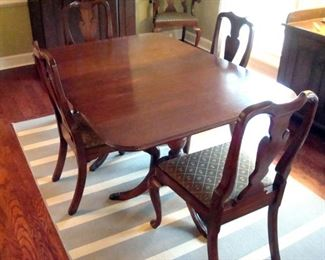 Vintage  mahogany Duncan Phyfe table with two extension leaves and pads and six Henkel Harris queen Anne style chairs.