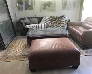 Antique Zebra rug.  Leather loveseat and ottoman