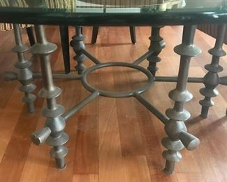 Detail of metal base on round, glass topped dining table in previous photo