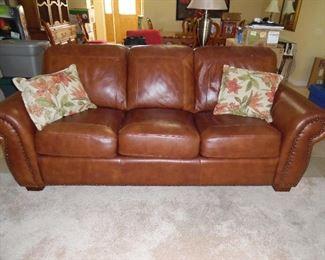 Genuine Leather, nail head trim.  Queen sleeper sofa - never used. Made by Leggett & Platt