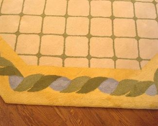 """Dining Room:  This large octagonal area rug has a cream field with green geometric print and a yellow/blue/green border.  It measures 16'  x  12'  10."""""""