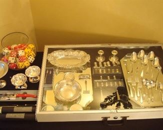 """Dining Room:  A large bowl of dice (each is 1-1/2""""  square and sold in pairs of same color) is near a few pieces of sterling, CUTCO knives, and silver-plate flatware.  Some closer photos follow."""