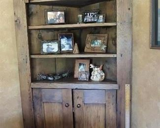Primitive Pine corner cupboard features four upper open shelves and three behind paneled doors.