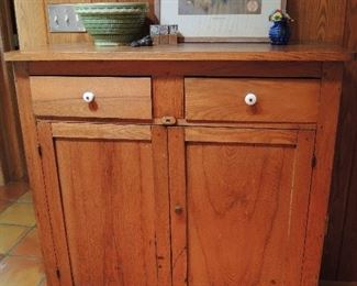 Antique oak jelly cupboard with original porcelain knobs on two drawers, paneled doors.