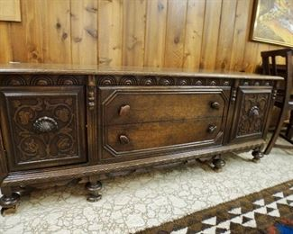Carved, low oak credenza with two dovetailed drawers, two cubbies with carved pulls and lots of detailed carving.