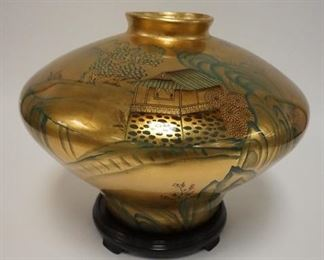 1002LARGE SCENIC ASIAN VASE, HAND PAINTED ON A GOLD BACKGROUND. COMES WITH CARVED WOODEN BASE. 12 3/4 H. APP 17 IN DIAMETER