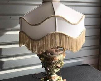 "Vintage Porcelain Lamp with flowers and cherubs with original fringed lampshade-in good working condition. Made in Italy late 1960's-early 1970's. Base 10"" Dia x 34"" H"