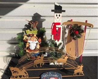 """Holiday Decor                                                                                         - Reindeer and sleigh card holder in bronze colored metal, new, 7"""" W x 28"""" L x 13"""" H - Painted metal Santa motif wreath, 9"""" W x 4"""" D x 18"""" H - Wooden snowman with greenery, 7"""" W x 26"""" H - Wooden sleigh with acorns, 14"""" W x 19"""" L - Hanging stone snowman, blue, 8"""" W x 12"""" H"""