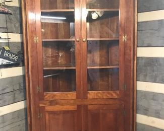 Large cherry corner cabinet with glass upper doors.