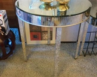 Larger of two round mirrored tables