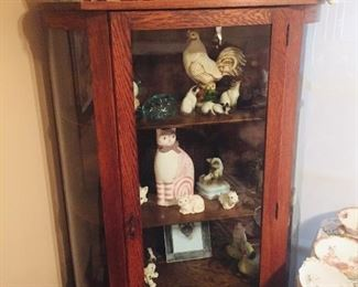 curved antique cabinet filled with artist made cats