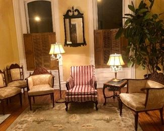 Golden high-armed chairs with matching side chairs, marble side table, sturdy red striped chair, crystal-trimmed lamps