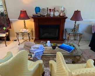 Living room brass & glass tables, Hickory wing back chairs, Stiffel table lamps, electric fireplace, vases, etc.