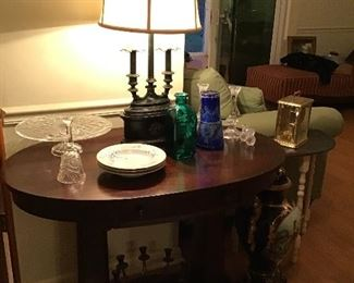Oval foyer table and ornate metal lamp