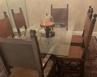 Glass top dining table with 6 wood and leather chairs.