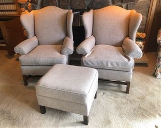 Neutral upholstered armchairs and ottoman