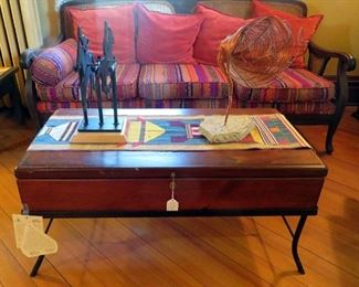Vintage wooden and wrought iron coffee table by 2 Day Design topped with a signed Charles Ringer Kinetic Racing Sculpture and  copper wire tornado sculpture. Fabulous antique wooden frame cane back couch with vibrant colored upholstery.
