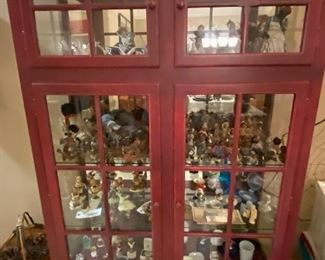 Red cabinet filled with collectibles. Cabinet is not for sale