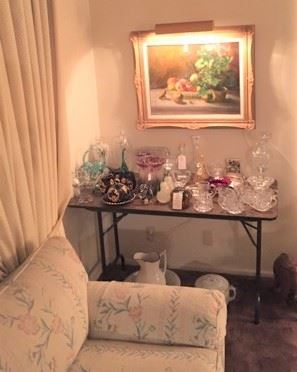 Crystal glasses & related glassware, a lit painting, and one of the sofas can be seen here.