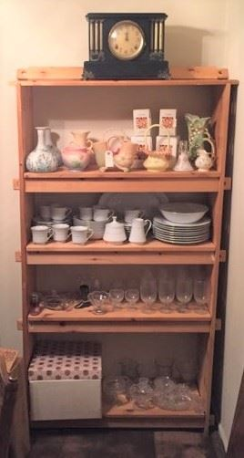 A mantle clock, matching dishware and glassware items are on this shelf unit.