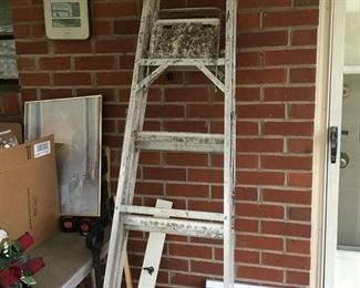 Ladder with wall racks with hooks.