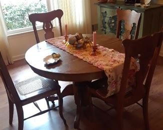 Round oak pedestal table with leaves,expanding to large oval; oak chairs