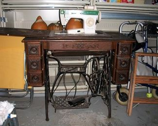 Vintage Singer cabinet with treadle; note old machine has been replaced