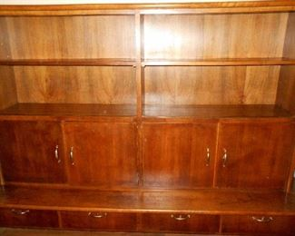 Large bookcase, doored display, possibly from a library or retail store/ shelves have slots for sliding glass