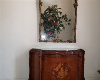 Louis XV style demi-lune chest with elaborate pictorial marquetry and floral carvings. Circa 1920.  Beautiful wall mirror with romantic painting of a couple.