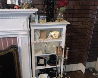 Lot 814 White Mirrored Fireplace Surround, White Shelves- Wooden white mirrored fireplace surround approx 7ft tall and 5ft wide; 8 candle holders; white dish; 4 pieces of clear glassware; two white wooden book shelves; sculpture; wall lamp with two lights; floral fireplace
