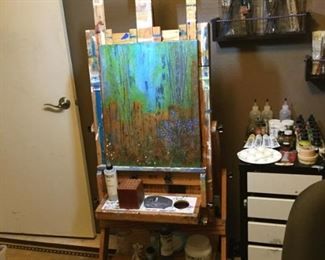 Artist easel in wood and wall shelves for paint supplies