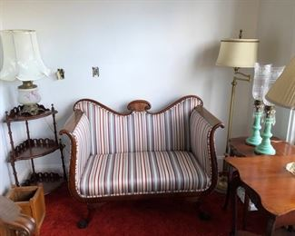 Parlor loveseat in excellent condition with assorted tables and lamps.